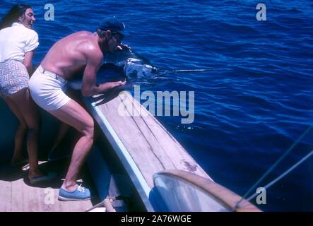BAJA CALIFORNIA, MÉXICO - JUNIO DE 1962: el actor y ex jugador de béisbol Chuck Connors (1921-1992) y la actriz prometido Kamala Devi (1934-2010) tirar un marlin en el barco mientras estaba en un viaje de pesca alrededor de junio de 1962, en Baja California, México. (Foto por Hy Peskin) (número de registro: X8569)