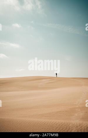 Persona camina alrededor en una duna de arena Foto de stock