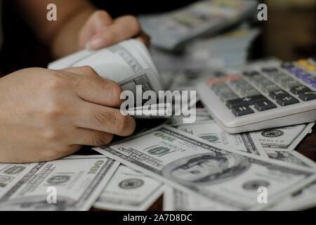 Mano sujetando el smartphone y calculadora de una pila de 100 dólares billetes montones de dinero Foto de stock