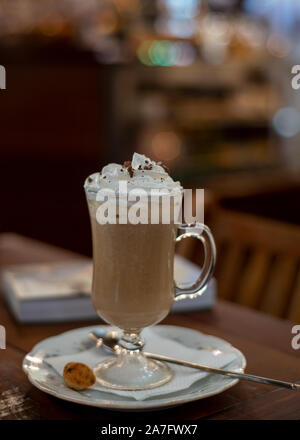 Café irlandés con crema batida en la parte superior de la placa blanca decorada con una cuchara en un restaurante, vista lateral y el enfoque selectivo