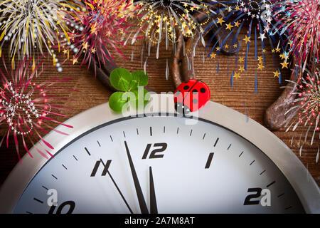 Concepto de partido la víspera de Año Nuevo con fuegos artificiales y reloj trébol de la suerte, como fondo de herradura