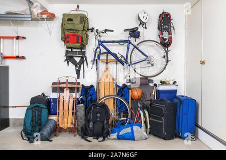 Deportes y viajes y equipo en montones en esquina de desordenado garaje suburbano.