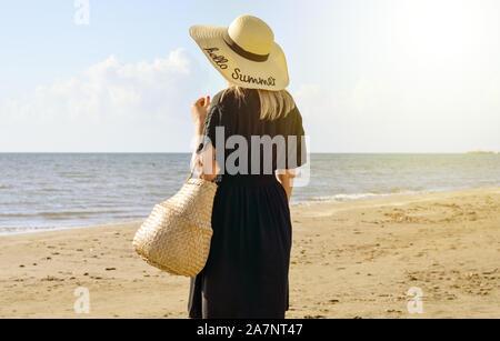 Vista trasera de un solo joven con sombrero de paja y cesta en su mano descansando en la playa . Filtro cálido brillante .