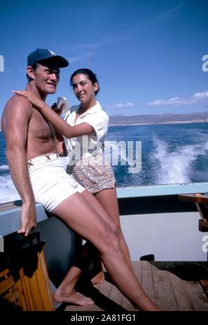 BAJA CALIFORNIA, MÉXICO - JUNIO DE 1962: el actor y ex jugador de béisbol Chuck Connors (1921-1992) y la actriz prometido Kamala Devi (1934-2010) Relájese en un barco durante un viaje de pesca alrededor de junio de 1962, en Baja California, México. (Foto por Hy Peskin) (número de registro: X8569)
