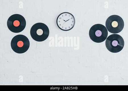 Los discos de vinilo y redondo reloj de pared de ladrillo blanco.