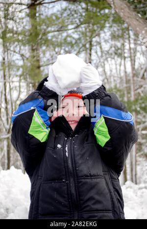 Con los brazos levantados, este niño está listo para lanzar una bola de nieve a usted