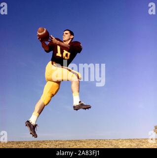 Jugadores de fútbol americano no identificado 1950 saltar en el aire con el balón (Foto por Hy Peskin)