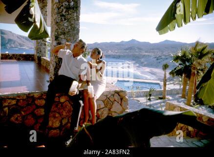 BAJA CALIFORNIA, MÉXICO - JUNIO DE 1962: el actor y ex jugador de béisbol Chuck Connors (1921-1992) y la actriz prometido Kamala Devi (1934-2010) sentarse fuera en el Cabo San Lucas Hotel durante un viaje de pesca alrededor de junio de 1962, en Baja California, México. (Foto por Hy Peskin) (número de registro: X8569) *** Local Caption *** Kamala Devi;Chuck Connors