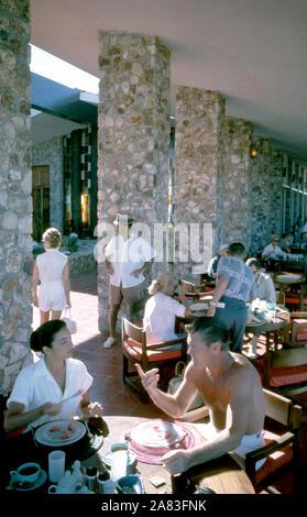 BAJA CALIFORNIA, MÉXICO - JUNIO DE 1962: el actor y ex jugador de béisbol Chuck Connors (1921-1992) y la actriz prometido Kamala Devi (1934-2010) desayunar afuera en el Cabo San Lucas Hotel durante un viaje de pesca alrededor de junio de 1962, en Baja California, México. (Foto por Hy Peskin) (número de registro: X8569) *** Local Caption *** Kamala Devi;Chuck Connors