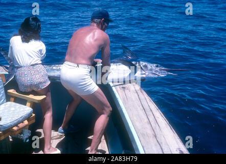 BAJA CALIFORNIA, MÉXICO - JUNIO DE 1962: el actor y ex jugador de béisbol Chuck Connors (1921-1992) y la actriz prometido Kamala Devi (1934-2010) tirar un marlin en el barco mientras estaba en un viaje de pesca alrededor de junio de 1962, en Baja California, México. (Foto por Hy Peskin) (número de registro: X8569) *** Local Caption *** Kamala Devi;Chuck Connors