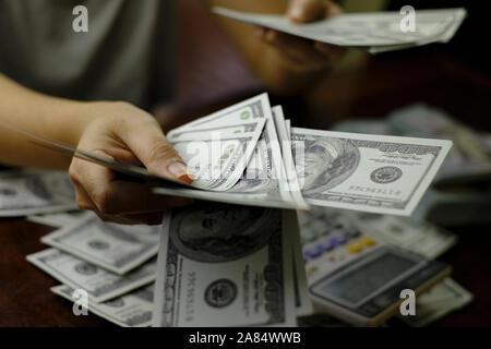 Los empresarios mujeres contando dinero en una pila de billetes de 100 dólares EE.UU. Foto de stock