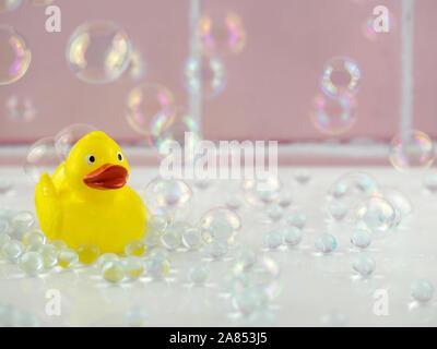 Patito amarillo en el cuarto de baño con burbujas y azulejos rosa