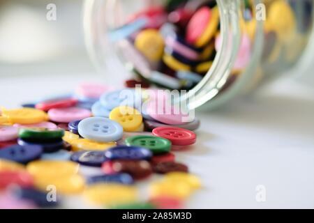 Gran grupo de coloridos cosiendo botones de plástico en una lata en la mesa, con espacio para copiar texto