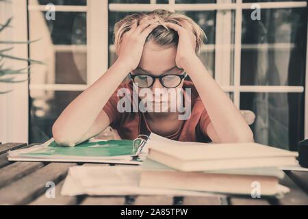 Cansado estudiante haciendo los deberes en casa sentados exterior con libros y periódicos. Chico cansado debido a su gran estudio. Niño dormido en el copybook