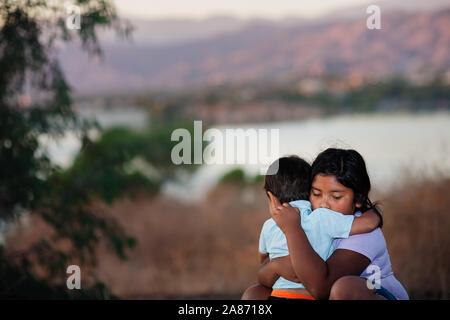 Hermano y hermana, separados de sus padres se abrazaban el uno al otro en un país extranjero, a través de un río.