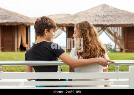 Par de bellas adolescentes, el primer amor. Guy abraza a una chica sentada en un banco y mirando el uno al otro