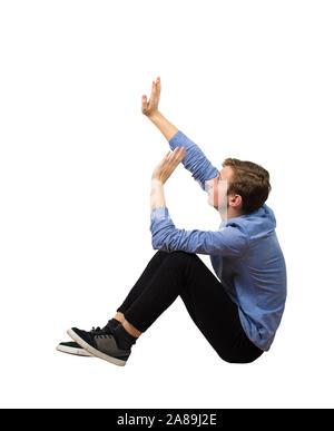 Vista lateral asustado muchacho adolescente sentado en el piso mantiene las manos elevadas para protegerlo de cualquier peligro, aislado sobre fondo blanco. Desamparado adolesce