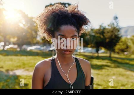 Retrato de un joven afroamericano deportivo con los auriculares en las orejas escuchando música mirando a la cámara - determina la aptitud de la mujer negra en