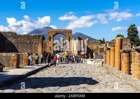 Vista de la via del Foro en la antigua ciudad de Pompeya con el arco de Calígula y el Monte Vesubio en el fondo. Pompeya, Italia, en octubre de 2019