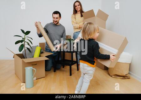 Joven familia se mudó a una nueva casa, desembalaje de cajas de cartón junto
