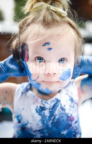 Un adorable pequeño infante, la niña ha divertido jugando con pinturas, colorantes obteniendo desordenado y con mucha diversión, rodada en un entorno doméstico