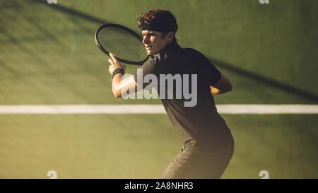 Los jugadores jóvenes a jugar al tenis en la pista dura. Golpear a un jugador de tenis profesional forehand durante un partido.
