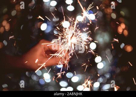 Mano sujetando una bengala de luz quema de fuegos artificiales bokeh de fondo. Navidad y Año nuevo concepto.