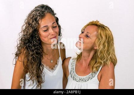 Intenso momento de complicidad entre madre e hija vestida de blanco sobre un fondo blanco.