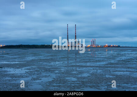 Poolbeg chimeneas gemelas / Pilas, tarde, marea baja ZPE de Sandymount Strand, Dublín, Irlanda. Hito de Irlanda. Poolbeg clausurada estación generadora. Foto de stock