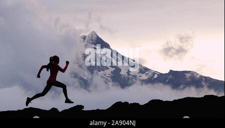 Correr mujer atleta silueta pista correr en el fondo de la cumbre de montaña