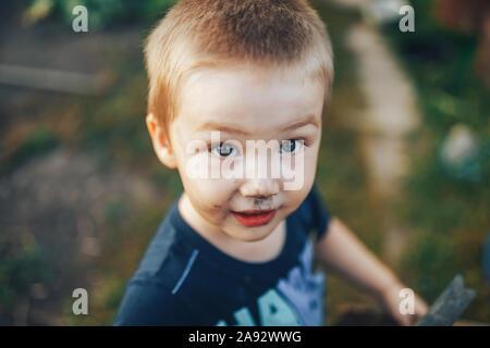 Muchacho rubio con cabello desaliñado sonriendo en un sillón negro