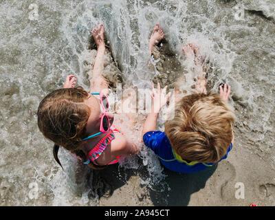 Un chico y una chica sentada en el surf en la playa.