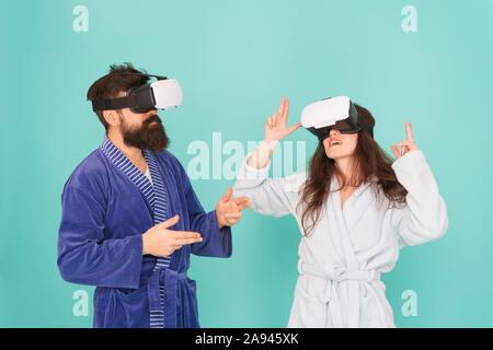 Familia par llevar gafas vr. chica y man hipster relájese en albornoz. La mañana empieza con la tecnología del futuro. Otra realidad es aquí. innovación en familia. Crea tu realidad. mundo de immagination.