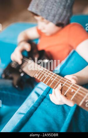 Primer plano de un niño tocando una guitarra eléctrica negra - mano recoge las notas sobre las cuerdas - Enfoque selectivo