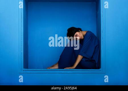 Hermosa joven mujer sentada en nichos sobre fondo azul. Foto de estudio.