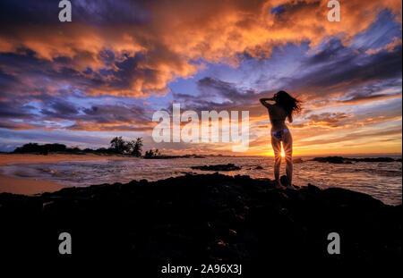 Una joven mujer se detiene para celebrar la puesta de sol sobre la playa Makalawena Hawaii