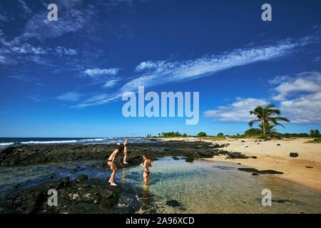 Tres mujeres jugando en una piscina natural en la Isla Grande de Hawai