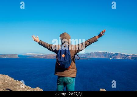 Hombre brazos levantados viajero sentirse libres y felices en la isla de Santorini en otoño. Admirando el paisaje turístico Caldera view