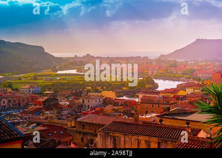 Vista desde arriba en la ciudad de Bosa con casas con tejados rojos, montañas con árboles verdes y el río Temo que fluye hacia el mar Mediterráneo. Ubicación th