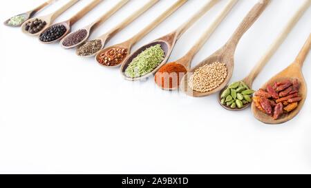 Especias y cucharas de madera contra el fondo blanco. Foto de stock