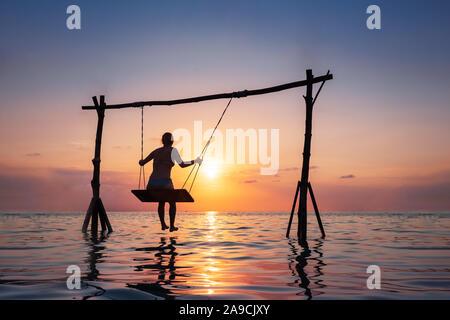 Niña alegre relajándose en la playa en columpio sobre el agua del mar al atardecer, holidays resort de vacaciones de verano Foto de stock
