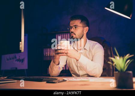 Foto de graves pensativo meditando Hombre bebiendo café no dormirse durante el turno de noche sentados delante de la pantalla para escribir código nuevo software