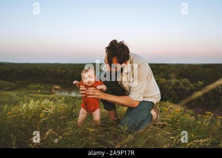 Padre de familia feliz al bebé al aire libre y estilo de vida familiar papá y niño caminando sobre el césped de las vacaciones de verano con kid paternidad Concepto de infancia padres d Foto de stock