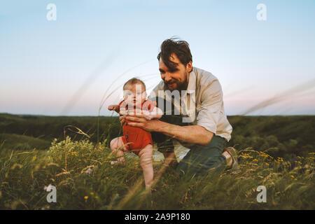 Padre de familia feliz y el bebé camina sobre el césped outdoors lifestyle papá y niño hija juntas las vacaciones de verano la paternidad niñez concepto padre Foto de stock
