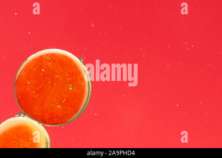 Gotas de aceite en agua. Resumen Antecedentes, dominante rojo con acentos de color amarillo-oro. Lugar para el texto. Foto de stock