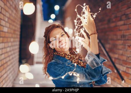 Mujer joven feliz jugando con las luces de hadas afuera en la ciudad, gran sonrisa