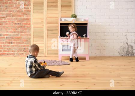 Concepto de familia y los niños. Niño chico jugando en el piso y cute little girl comer dulces en la cocina de juego en la gran sala vacía copia espacio