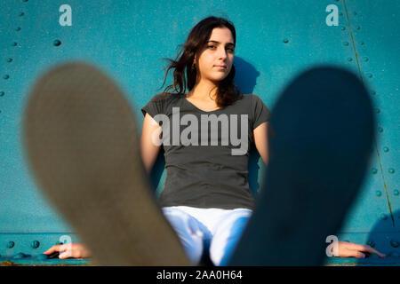 Retrato de una niña sentada en la calle con pared azul