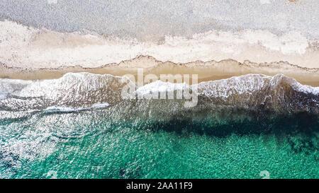 Vista superior de antena con zumbido de una playa mediterránea con aguas cristalinas y arena pequeñas olas