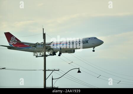 Chicago, Illinois, Estados Unidos. Un Jumbo 747 Cargolux tiene cerca de minas con líneas telefónicas como la carga jet hace su aterrizaje final.